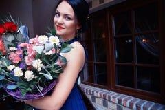 Muchacha hermosa con un ramo grande de flores Foto de archivo libre de regalías