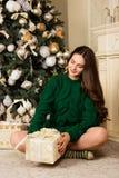 Muchacha hermosa con un regalo a disposición, sentándose en la alfombra cerca del árbol de navidad Fotos de archivo libres de regalías