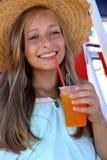 Muchacha hermosa con una bebida helada, sombrero de paja en la playa Imágenes de archivo libres de regalías