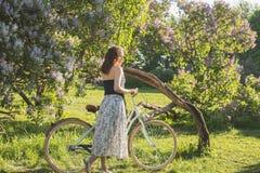 Muchacha hermosa con una bicicleta Imágenes de archivo libres de regalías