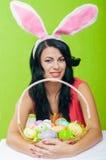Muchacha hermosa con una cesta de huevos de Pascua i Fotografía de archivo