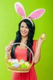 Muchacha hermosa con una cesta de huevos de Pascua i Foto de archivo libre de regalías
