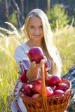 Muchacha hermosa con una cesta de manzanas Imágenes de archivo libres de regalías