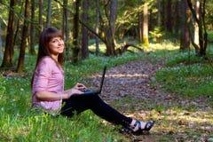 Muchacha hermosa con una computadora portátil en el bosque Imagenes de archivo