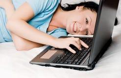 Muchacha hermosa con una computadora portátil en la cama Imágenes de archivo libres de regalías