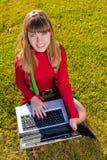 Muchacha hermosa con una computadora portátil en la hierba Foto de archivo libre de regalías