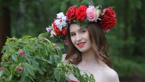 Muchacha hermosa con una guirnalda de flores en su cabeza almacen de video