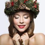 Muchacha hermosa con una guirnalda de las ramas y de los conos de árbol de navidad Imagen del Año Nuevo Cara de la belleza Imagen de archivo