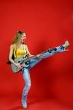 Muchacha hermosa con una guitarra que grita Imagen de archivo libre de regalías
