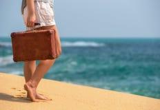 Muchacha hermosa con una maleta vieja del vintage en una playa Imagenes de archivo