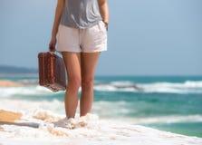 Muchacha hermosa con una maleta vieja del vintage en una playa Foto de archivo libre de regalías