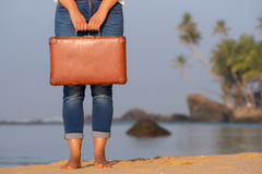 Muchacha hermosa con una maleta vieja del vintage en una playa Fotografía de archivo libre de regalías