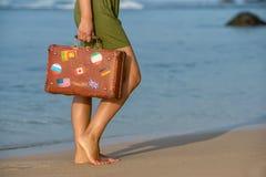 Muchacha hermosa con una maleta vieja del vintage en una playa Imágenes de archivo libres de regalías