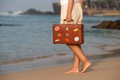 Muchacha hermosa con una maleta vieja del vintage en una playa Fotos de archivo