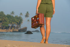 Muchacha hermosa con una maleta vieja del vintage en una playa Foto de archivo