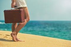Muchacha hermosa con una maleta vieja del vintage en una playa Imagen de archivo libre de regalías