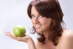Muchacha hermosa con una manzana verde Imagen de archivo