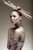 Muchacha hermosa con una piel de bronce, un maquillaje pálido y accesorios inusuales Imagen de la belleza del arte Cara de la bel Imágenes de archivo libres de regalías
