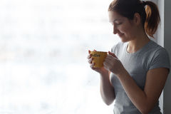 Muchacha hermosa con una taza amarilla con café de la inscripción en la ventana Fotos de archivo libres de regalías