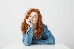 Muchacha hermosa contenta con el pelo rizado y las pecas que sonríe soñando sentarse en la tabla sobre el fondo blanco Fotografía de archivo libre de regalías