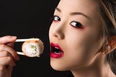 Muchacha hermosa coreana del adolescente con maquillaje brillante que come un rollo Fotos de archivo