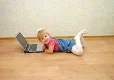 Muchacha hermosa de 3 años que mienten cerca de la computadora portátil Imagen de archivo