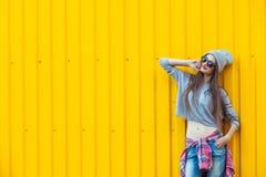 Muchacha hermosa de Bool sobre la pared amarilla Foto de archivo