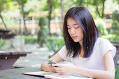 Muchacha hermosa de China de Asia de la universidad tailandesa del estudiante que usa su teléfono elegante Imagen de archivo libre de regalías