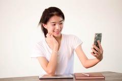 Muchacha hermosa de China de Asia de la universidad tailandesa del estudiante que usa su teléfono elegante Selfie Imagen de archivo
