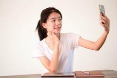 Muchacha hermosa de China de Asia de la universidad tailandesa del estudiante que usa su teléfono elegante Selfie Imagenes de archivo