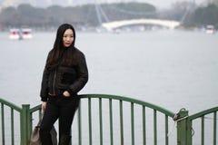 Muchacha hermosa de China que se inclina contra la cerca Fotografía de archivo