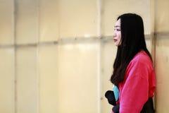 Muchacha hermosa de China que se inclina contra la cerca blanca Foto de archivo libre de regalías