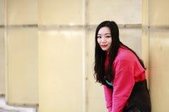 Muchacha hermosa de China que se inclina contra la cerca blanca Imagen de archivo