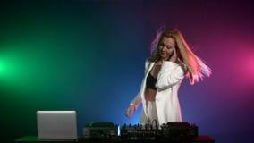 Muchacha hermosa de DJ en la chaqueta blanca que juega música almacen de video