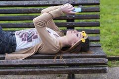 Muchacha hermosa de Happines con el teléfono elegante que miente en el banco Imagen de archivo libre de regalías