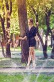 Muchacha hermosa de la bailarina en la ropa casual que presenta en un fondo borroso de los árboles del parque en fondo imágenes de archivo libres de regalías