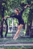 Muchacha hermosa de la bailarina en la ropa casual que presenta en un fondo borroso de los árboles del parque en fondo imagenes de archivo