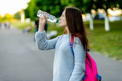 Muchacha hermosa de la colegiala Naturaleza del verano Él sostiene una botella de agua y bebe Brunette con el pelo largo Detrás d Fotos de archivo libres de regalías