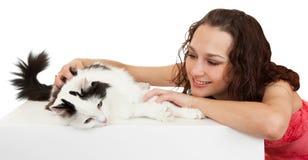 Muchacha hermosa de la comunicación con un gato preferido. Imagen de archivo