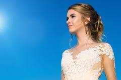 Muchacha hermosa de la elegancia en vestido beige en el cielo azul del fondo Foto de archivo