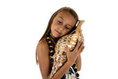 Muchacha hermosa de la isla que se sostiene y que escucha una concha marina Imagen de archivo libre de regalías