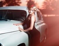 Muchacha hermosa de la moda en el estilo retro que se sienta en coche viejo Fotos de archivo libres de regalías