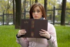 Muchacha hermosa de la mujer del pelirrojo que engaña alrededor con un libro Fotografía de archivo libre de regalías