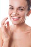 Muchacha hermosa de la mujer joven que aplica la crema en su cara aislada imágenes de archivo libres de regalías