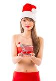 Muchacha hermosa de la Navidad de Papá Noel con la pequeña carretilla de las compras en wh Imagen de archivo