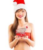Muchacha hermosa de la Navidad de Papá Noel con la pequeña carretilla de las compras en wh Imagen de archivo libre de regalías