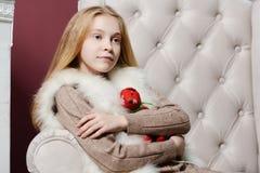 Muchacha hermosa de la Navidad que abraza un juguete que se sienta en una silla blanca cerca de la chimenea y del árbol de navida Fotos de archivo