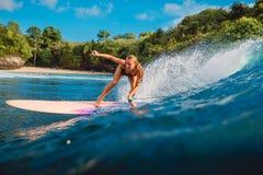 Muchacha hermosa de la persona que practica surf en la tabla hawaiana Mujer en el océano durante practicar surf en Bali Foto de archivo libre de regalías
