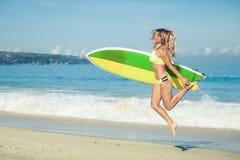 Muchacha hermosa de la persona que practica surf que camina en la playa Imagen de archivo libre de regalías