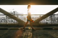 Muchacha hermosa de la puesta del sol con un monopatín Imagen de archivo libre de regalías